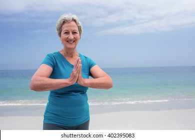Portrait of happy senior woman in lotus position on the beach