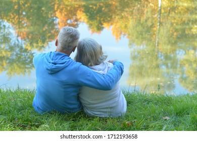 Portrait von glücklichen Senioren und Mann im Park sitzend am Teich
