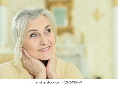 Portrait of happy senior woman in posing at home
