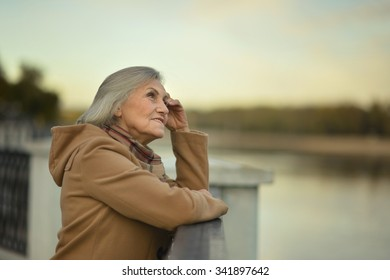 Portrait of a happy senior woman posing near river