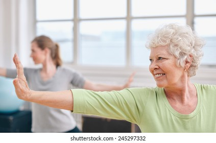 Portrait of happy senior woman practicing yoga at gym class. Elderly woman stretching her arms .