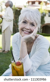Portrait of happy senior woman sitting with glass of juice