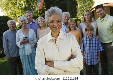 Portrait of happy senior woman standing with hands folded and family in background at garden