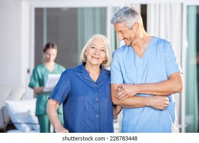 Portrait of happy senior woman standing with male caretaker at nursing home yard