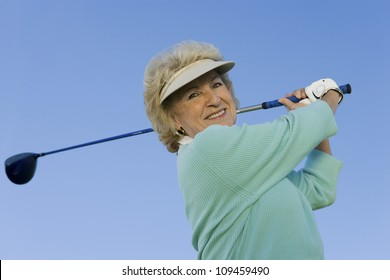 Portrait of a happy senior woman swinging a golf club against clear sky