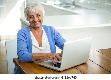 Portrait of happy senior woman using laptop while sitting at table