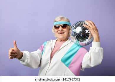 Portrait of happy senior woman in white sportswear holding discoball in hands, posing isolated over purple background