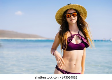 portrait of happy sexy girl in pink bikini posing against sea in