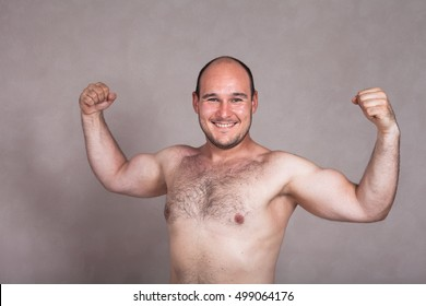 Portrait of happy shirtless man posing and showing his strong arms and hairy body.