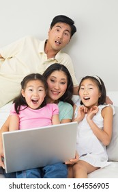 Portrait of a happy shocked family of four using laptop at home
