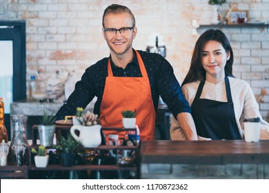 Portrait of happy shop partners wearing an apron attractive caucasian Male and female asian Barista cafe restaurant owner smile with confident and warm welcome successful business place