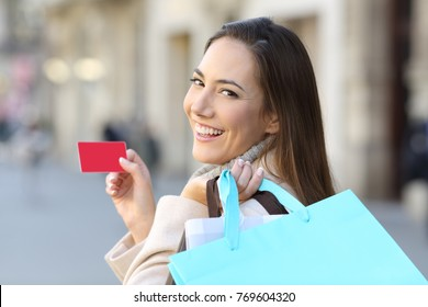 Portrait of a happy shopper holding shopping bags and credit card on the street