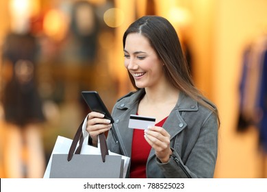 Portrait of a happy shopper paying on line with credit card in a mall