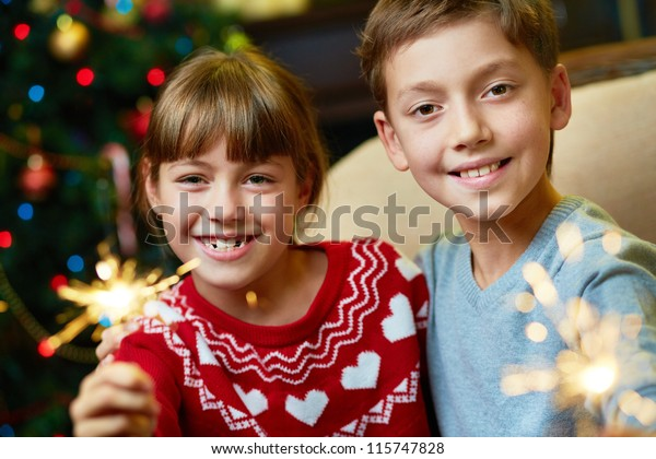 Portrait of happy siblings with Bengal lights on Christmas evening