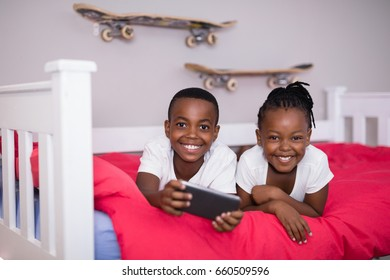 Portrait of happy siblings with mobile phone lying on bed at home