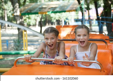 Portrait of happy sisters enjoying themselves on carousel