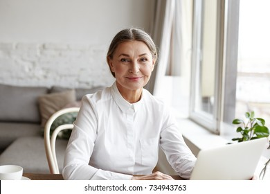 Portrait of happy skilled middle aged woman life coach, business consultant, psychologist or medical advisor smiling joyfully at camera, working on laptop, enjoying her job, helping people online