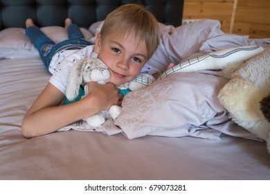 portrait of happy small boy on the bed with a toy