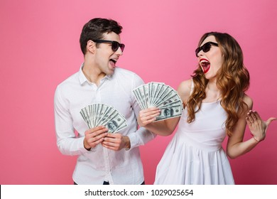 Portrait of a happy smartly dressed couple holding bunch of money banknotes and celebrating isolated over pink background