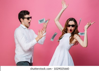 Portrait of a happy smartly dressed couple celebrating while standing under money shower isolated over pink background