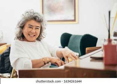 Portrait of happy smile Asian elderly grandmother playing piano in living room at home, old woman activity lifestyle after retirement , living quality and insurance concept