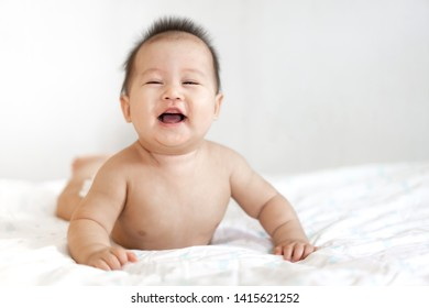 Portrait of happy smile baby relaxing on the bed