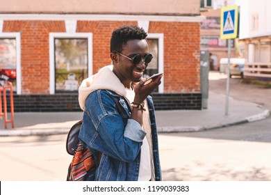 Portrait happy smiling african man with smartphone using voice command recorder or calling while walking on city street