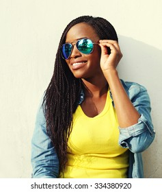 Portrait happy smiling african woman in colorful clothes and sunglasses in profile