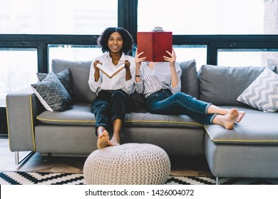 Portrait of happy smiling afro american female looking at camera while sitting barefoot on comfortable couch near friend reading interesting literature bestseller in apartment with stylish interior