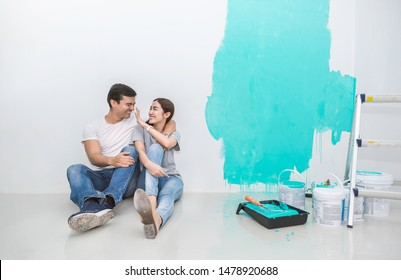 Portrait of happy smiling asian couple renovating painting wall house. Mother father repairing paint wall at home. Man and woman together love lifestyle concept with copy space.