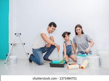 Portrait of happy smiling asian family renovating painting wall house. Mother father and child daughter repairing paint wall at home. Together love lifestyle concept with copy space.