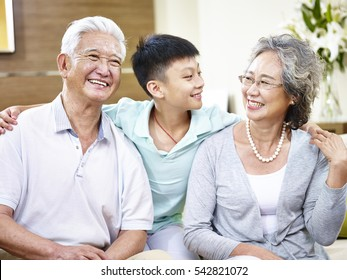 portrait of happy smiling asian grandparents and grandson.