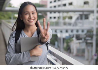 portrait of happy smiling asian woman college student pointing up 3 fingers, three points pose; winning, third concept in city campus environment
