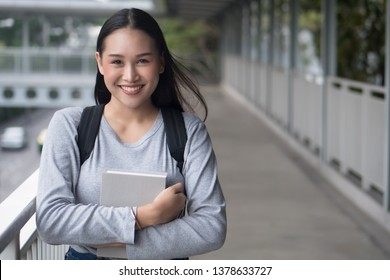 portrait of happy smiling asian woman college student in city campus environment