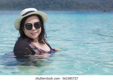 Portrait of Happy Smiling Asian Woman, Wearing Sunglasses and Weaving Hat, in Perfect Crystalline Blue Water Ocean. Happy Holiday Concept.