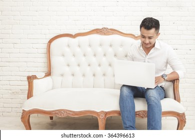 portrait of Happy smiling asian young man sitting on sofa while watching and working on laptop at home
