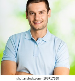 Portrait of happy smiling attractive young man, outdoors