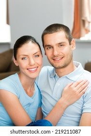 Portrait of happy smiling attractive young couple at home