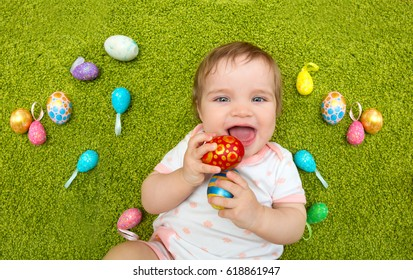 Portrait of happy smiling baby with Easter eggs lying down on a green rug, top view. Kids celebrate Easter.