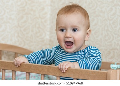 Portrait of happy smiling baby sitting in a baby cot.