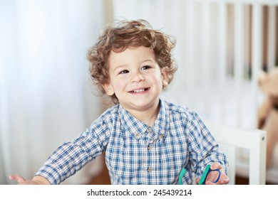 Portrait of happy smiling beautiful little boy in babyroom - checked shirt