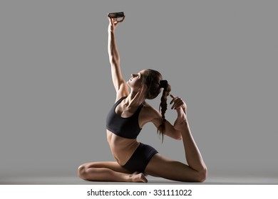 Portrait of happy smiling beautiful young fit woman in sportswear doing stretching sport exercise, sitting in One Legged King Pigeon Posture, taking selfie with mobile phone, studio, gray background