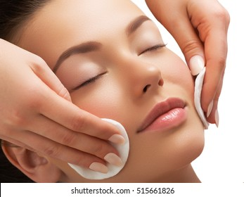 Portrait of happy smiling beautiful young woman cleaning skin by cotton pad, at spa salon. Beautiful face of a young woman. Woman beauty face portrait with healthy skin. Natural beauty concept
