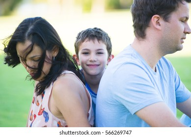 Portrait happy smiling boy between parents, who show negative body language, no interaction, are angry, having stress, problems in family relationship.