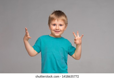Portrait of happy smiling boy in blue t-shirt. Attractive kid in studio.