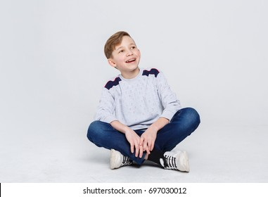 Portrait of happy smiling boy in braces sitting on the floor at white studio background. Kid in casual clothes looking up, copy space