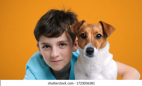 Portrait of happy smiling boy and dog Jack Russell Terrier hugs her with tenderness and look at camera on yellow background. Pet care. Emotions of people. Childhood. Life style