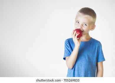 Portrait happy, smiling boy eats an red apple. Funny child holding an apple. Looking at camera. The concept of a healthy lifestyle, organic vegetarian food.