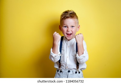 Portrait of happy smiling boy with hands up. Stylish child boy. Excited kid looking in camera isolated on yellow background. Shoked and surprised little boy. Back to school.