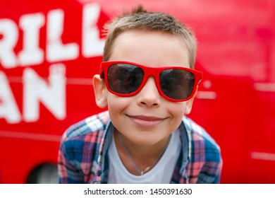 Portrait happy smiling boy wearing a checkered shirt and sunglasses in city